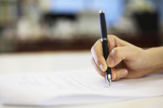 書類を書く手の画像