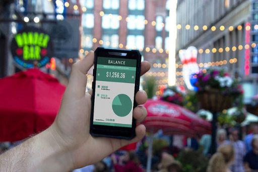 街中で金額が表示されたスマートフォンと手に持っている様子