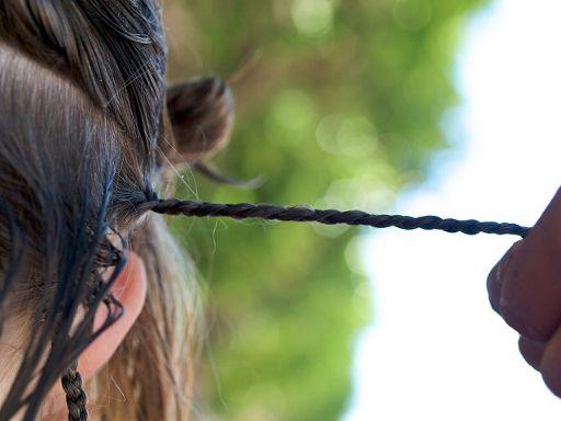 髪の毛を細かく編んでいる様子