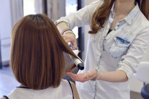 美容師が女性の髪にコテを当てる