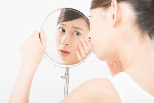 鏡で顔を気にする女性