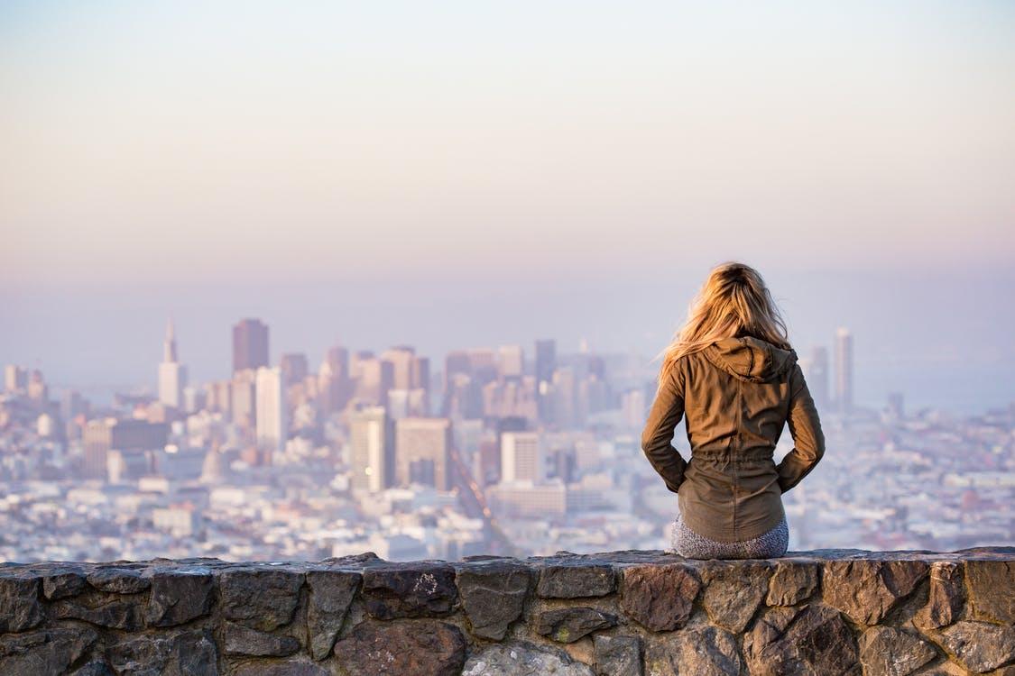 塀の上に座る女性
