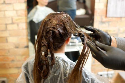 髪をカラーリングされる女性