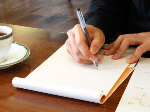 ノートに何かを書いている手