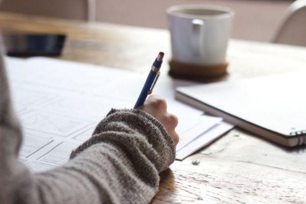 本に書いて勉強する女性