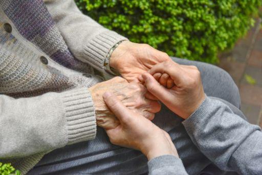 老人の手をとる女性