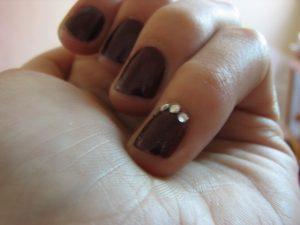 茶色ネイルにラインストーンが乗った小指