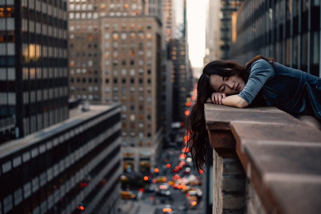 ビルの上で横になる女性