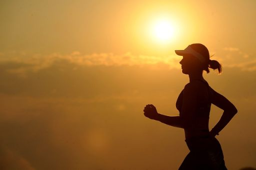 夕日を背景に走る女性