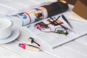 ビビッドピンクのリップと雑誌やメガネ