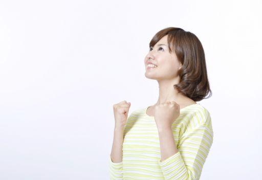 ガッツポーズをして上を見上げる女性