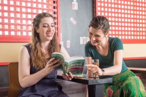 ガイドブックを見て笑う外国人