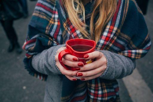 赤いマニキュアをした女性がマグカップを持っている