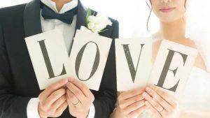 LOVEと書かれた紙を持つ新郎新婦