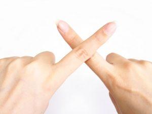 指でバツをしている