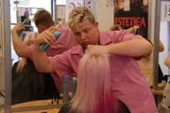 女性の髪をスタイリングする男性