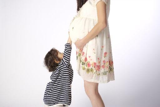 こどもが妊娠中の母親のおなかに手を当てている様子